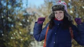 4K close up shot of happy woman promenading in the winter park who happily gestures with her hands