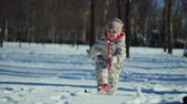 4K Cheerful child walks in the high snow in winter. The child wears warm overall Stock Footage