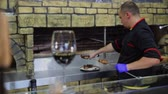 chef uniform : The first plan is a glass of wine, background Chef puts prepared meat on the plate. Stock Footage