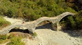 órbita : Aerial view of a tourist crossing Plakidas arched stone bridge of Zagori region Vídeos