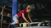 bunda : sexy blonde in a garage repairs a car