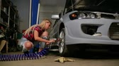 égalité des sexes : sexy blonde in a garage repairs a car