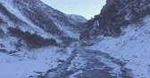 Flying over a frozen mountain river. Drone Aerial Flight in the mountains in winter. Стоковые видеозаписи
