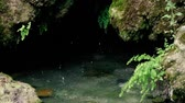 underground water : Slow motion footage. Drops drip into the water in a small cave