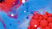 Amazing red and blue bubbles of paint on the oil surface. Paint in oil.