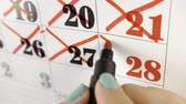 memorando : Female hand crosses with red marker the calendar day 28. Slow motion shot. Close up