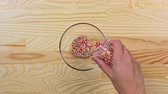 небольшой : Woman pours multi-colored sugar sprinkles dots into a glass bowl, top view Стоковые видеозаписи