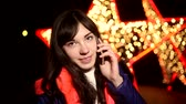 holding : woman girl talking on the phone at night on a smartphone background bokeh star Stock Footage