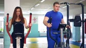 fitness : Girl man on simulator sports ellipsoid involved with trainer