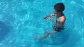 boy swimming in the pool kids playing slow motion video Стоковые видеозаписи