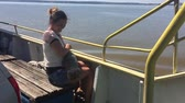woman with a dog on a ship sailing on the river slow motion video. girl with a pet on the deck of a ship floating on water