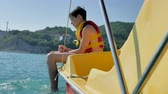 生活方式 : boy teenager on a yacht in the open ocean water on a catamaran