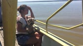 woman with a dog on a ship sailing on the river slow motion video. girl with pet on the deck of a ship floating on the water slow motion video Стоковые видеозаписи