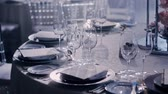 buquê : Camera moving aroung a wedding decorated table from left to right on dark background and smoke or haze, and light sparkles in dishes.