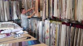 swatches : Clothing Designer Man Is Standing In Clothing Factory And Using Paper Tablet While Samples Stitched In The Background. Decorator Man Leafing Through Tissue Samples