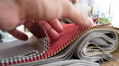 swatches : Tissue Samples, Choice of Fabrics for Upholstery. Decorator Man Leafing Through Tissue Samples. Decorator Or Tailor Touching Textiles Textures Fabric Swatches Stock Footage