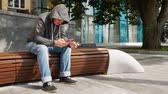 betörő : Hooded man holding red smartphone and credit or debit card and buy online outside near tree on a brown bench