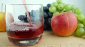 żurawina : Red Juice Flows In Glass On The Background Of Ripe Blue And White Grapes And Red Apple. Apple Juice in Glass. Pouring Grape Juice Into Glass Placed Near Fruits on White Background Isolated Wideo