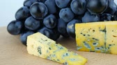 hard cheese : Hard Cheese With Mold, Dark Blue Grapes On the Wooden Surface Rotations on White Background Isolated