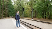 bag check : A young man is waiting for a train on an apron and looks at a wristwatch. A railroad station in the forest in the autumn. Student traveler is nervous because of late train Stock Footage