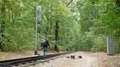 gündelik : Young man walks between the railway rails. A railroad station in forest in the autumn. Student traveler with a black backpack and in blue jacket walks away from the camera