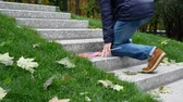 symbol of respect : Man With American USA Flag Rises on Granite Steps on Memorial with Memory Wall or Tombstone around Green Grass. Concept of Memorial Day or Veterans Day 11th November in America. Autumn, Fallen Leaves Stock Footage