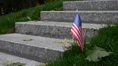 veterán : Man Rises and Goes on Granite Steps on Memorial with a Memory Wall or Tombstone around Green Grass. Concept of Memorial Day or Veterans Day in America With American USA Flag