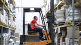 stacking : Warehouse worker driver in uniform moving cardboard boxes by forklift stacker loader. Forklift pallet with boxes in large modern warehouse