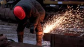 spojit : Worker in helmet and specially working clothes welds an iron beam with sparks in construction site. Welding sparks of beam steel from welding technician or sparks cut steel with fire gas Dostupné videozáznamy