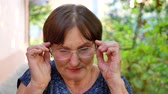 alerji : Portrait of elderly woman with eyeglasses has eyesight problems. She is rubbing his nose and eyes because of weariness