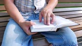 písmo svaté : Reading and studying the Holy Bible outdoor in a park in the summer on a sunny day