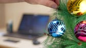 ocasião : Clerk hanging blue Christmas ball on a Christmas tree at work place with notebook background Stock Footage