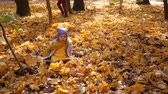 tossing : Little cute girl in blue neon color hat and yellow scarf throwing or throwing up leaves at park in autumn and trees. Mother knits a yellow leaf wreath background Stock Footage