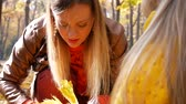 věnec : Mother knits a yellow leaf wreath together with daughter at park in autumn with colorful leaves and trees background Dostupné videozáznamy