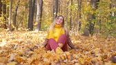 Cute woman in yellow scarf throwing or throwing up leaves at park in autumn and trees background
