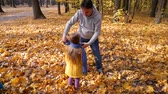 Loving and caring dad playing with his daughter at park in autumn with colorful leaves and trees background. Family time or leisure together concept