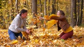Stylish young happy smiling couple play on a sunny day in autumn park. Lifestyle, love, relationship, family and people concept. Young family having fun outdoors. Enjoying autumn time together. Стоковые видеозаписи