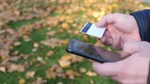 Man using mobile smartphone and credit card on a background of green grass with yellow fallen leaves in autumn. Shopping online concept Стоковые видеозаписи