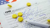 tax time : Yellow pills falling down on american 1040 Individual Income Tax return form
