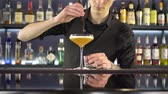 strainer : Barman making fresh alcoholic drink into the glasses on bar counter