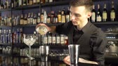 colador : Barman making alcoholic drink into the glasses with ice cubes on the bar counter