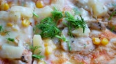 Fresh hot pizza with hot cheese, pineapple, corn kernels and dill