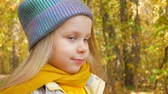 Little cute girl in blue neon color hat and yellow scarf is smiling at park in autumn with colorful leaves and trees background