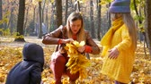 Mother knits a yellow leaf wreath together with two children at park in autumn with colorful leaves and trees background