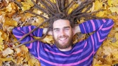 Smiling Young Man with Dreadlocks Lying on Fallen Leaves in Autumn Park
