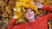 Smiling happy woman portrait with wreath, lying in autumn leaves