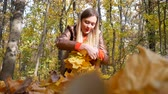 Cute woman knits a yellow leaf wreath at park in autumn with colorful leaves and trees background