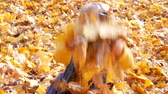Little cute girl in blue scarf throwing up leaves at park in autumn