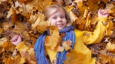 Smiling happy little girl lying and tossing or throwing fallen leaf in autumn in park