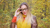 Portrait of beautiful woman wearing yellow glasses at park in autumn with colorful leaves and trees background